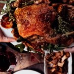 roast chicken being handed across table